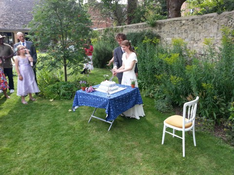 Matthew and Katherine cut the cake in the garden of the Quaker Meeting House.