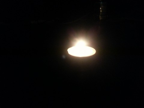 A tealight candle burning in the dark.