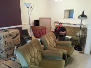Alec among furniture and boxes.